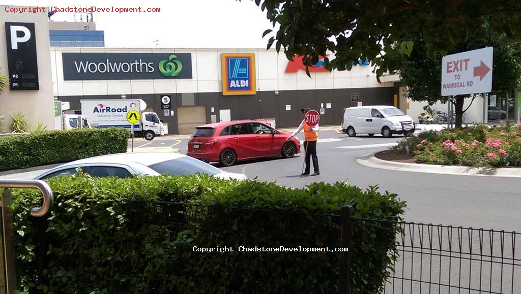 A traffic controller directs motorists at the Middle Rd roundabout - Chadstone Development Discussions